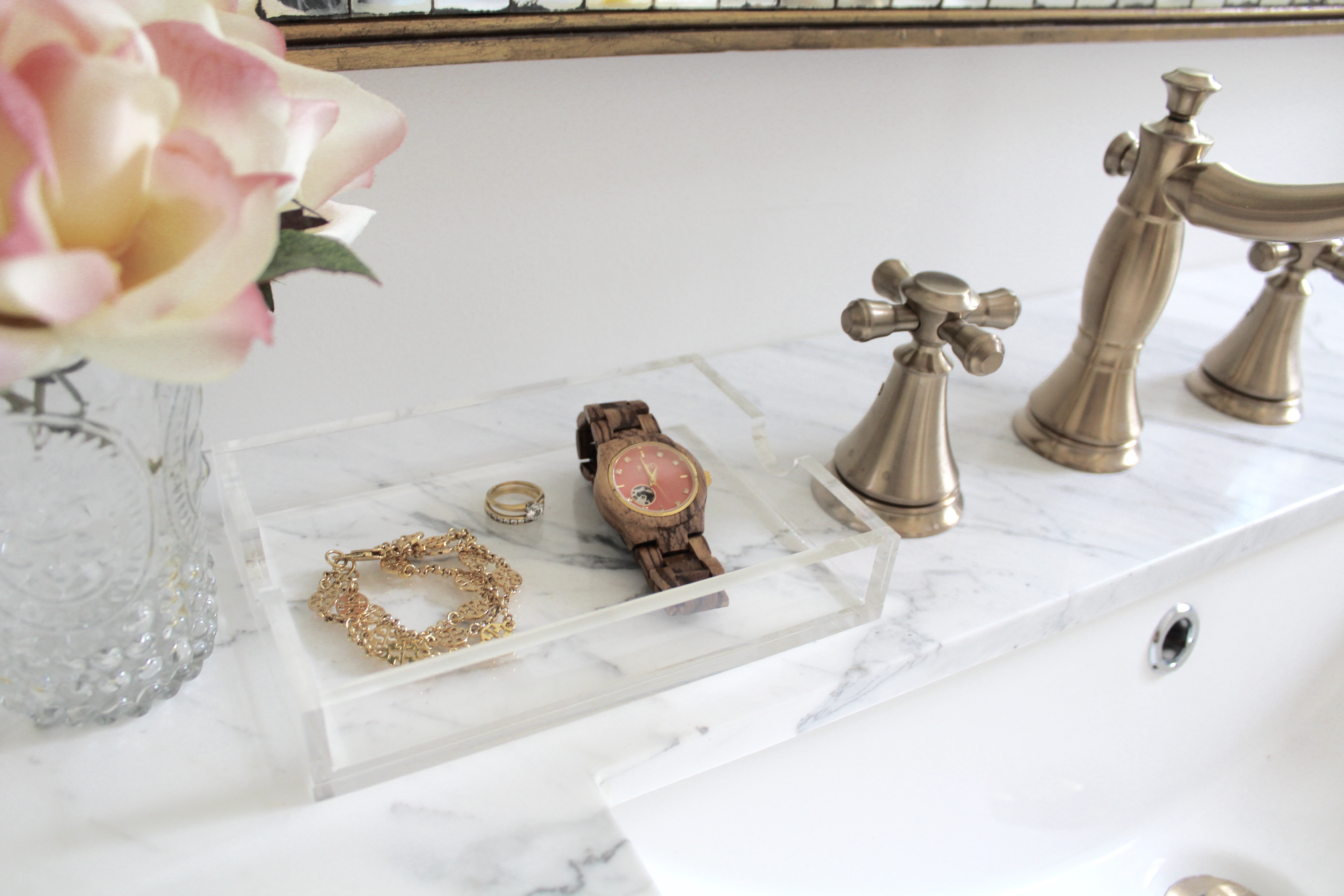 marble_delta_faucet_champagne_bronze_lucite_tray_wood_watch